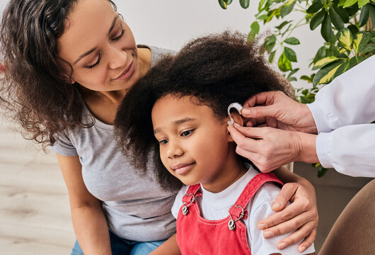Hearing treatment for a child. African American girl with her mother during installation hearing aid by her audiologist