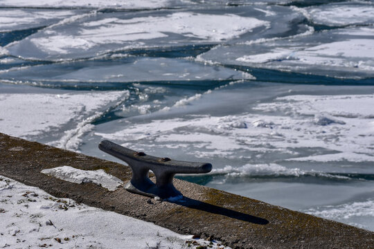 Close up of dock and mooring cleat and icy winter background. Concept of drowning, danger and cold water.