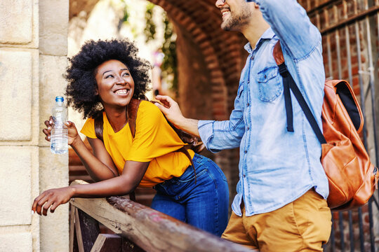 Young smiling attractive multicultural hipster couple flirting outdoors. Woman leaning on the railing, drinking water and looking at her caucasian boyfriend.