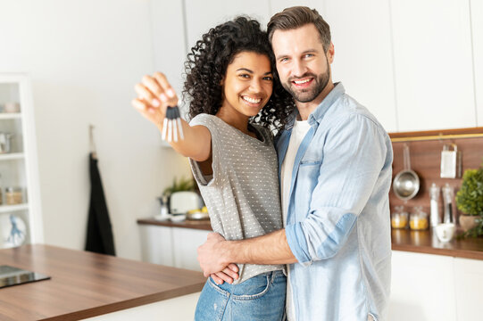 Excited multiracial couple in love move in a new apartment. Cheerful African woman in embrace of a caucasian guy holds the keys, the newlywed look at the camera and smile