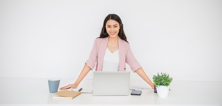 Portrait of smiling beautiful business asian woman in pink suit working in office desk virtual computer. Small business people employee freelance online sme marketing start up e-commerce, woman on top