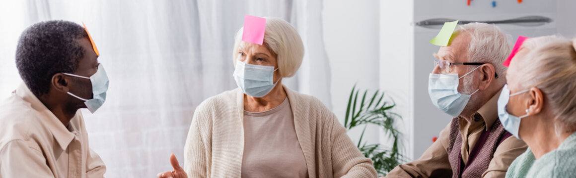 retired people in medical masks with sticky notes on foreheads discussing while playing game with multiethnic friends, banner