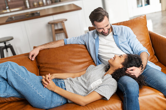 A multiracial couple in love enjoys time together at home, spends a lazy weekend on the couch in cozy living room. African woman lies on the laps of her boyfriend in relaxed pose, look to each other