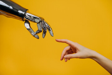 Obraz Robotic bionic hand and a woman's hand pulling fingers together on a yellow background close-up, the concept of human interaction and modern technology - fototapety do salonu