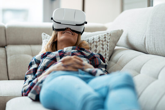 Beautiful young woman using virtual reality headset and enjoying the moment lying on couch at home.