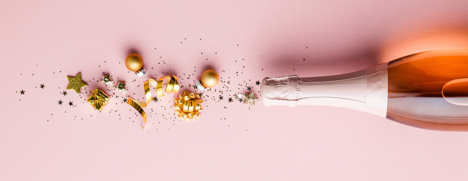 Directly Above Shot Of Champagne Bottle And Christmas Decoration Against Pink Background