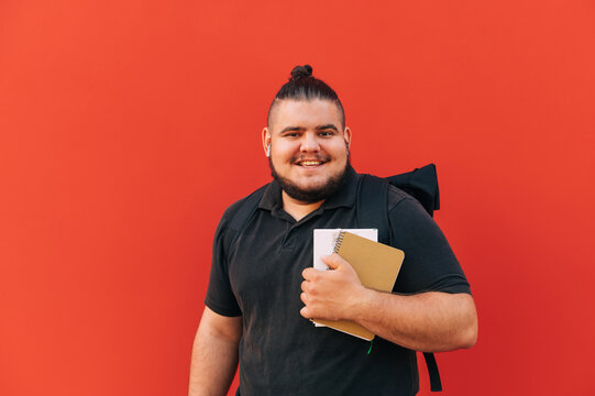 Portrait of happy overweight student on red background, wearing dark clothes, standing with books and notebook in hands and backpack on his back on red background and smiling.