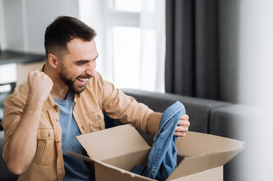 Overjoyed happy man unpacked his parcel, happy about getting a long expected order. Caucasian modern guy shopping in internet stores, buying new clothes online, online shopping concept