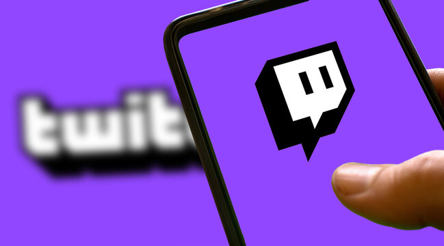 Purple twitch logo on a smartphone screen with purple background and blur twitch lettering. Gamer streaming website icon