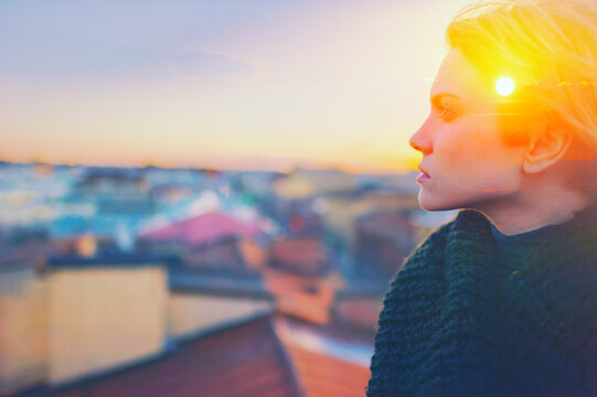 Sad lonely young woman portrait. Alone teen girl looking at sun in sky. Lady face profile on sunset roof. Female person mental health, urban life mood, abstract inner stress, people mind power concept