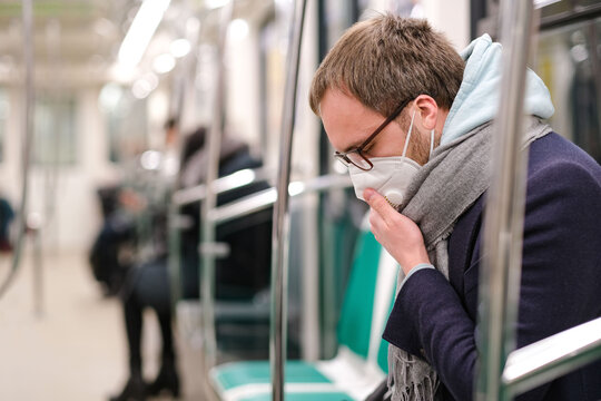 Side View Of Man Wearing Mask With Hand On Mouth Sitting In Train