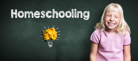 young smiling girl in front of blackboard with message HOMESCHOOLING