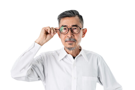 An old serious Asian man has looked at the camera and moving his glasses to see more clearly. Set over the white background. Senior, lonely retired and eye problem Concept