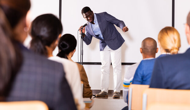 Expressive male lecturer speaking at corporate motivational coaching and training conference