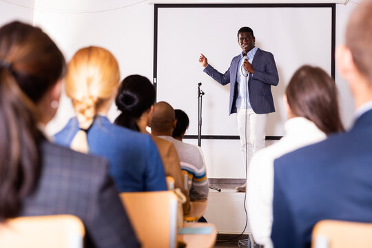 Positive male lecturer speaking at corporate business coaching and training conference