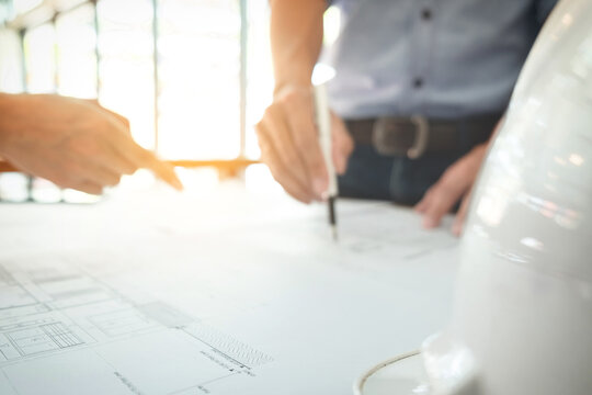 Cropped Hands Of Business People Discussing Blueprint At Desk In Office