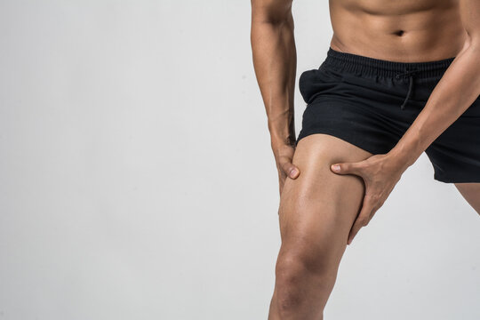 Midsection Of Man Suffering From Thigh Pain Against White Background