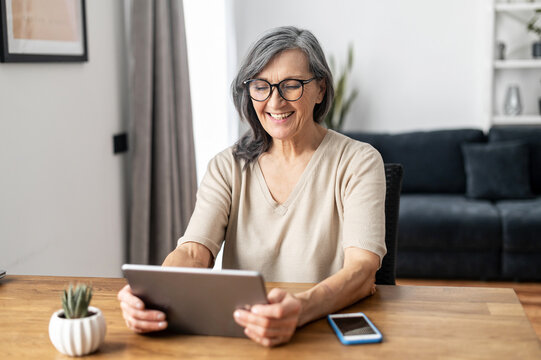 Merry mature middle-aged woman spends leisure time at home using a digital tablet. Cheerful modern senior lady holds computer, watching funny movies and laughs. Leisure and technology concept