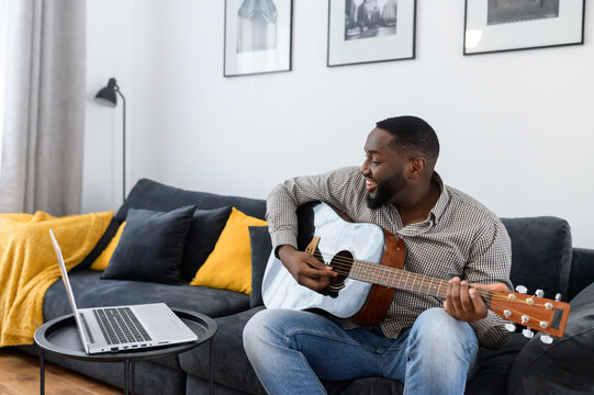 Young African American male musician or teacher playing guitar during an online concert lesson at home while isolated, sitting on the sofa, using laptop to stream record music, chatting with friends