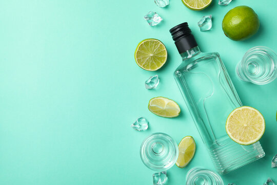 Bottle and shots of vodka, limes and ice on mint background, top view