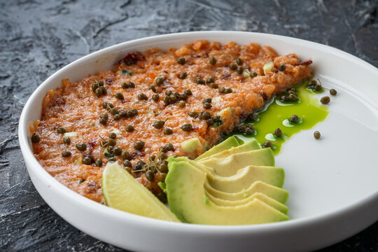 salmon tartare with avacado in a white plate on a dark background close-up