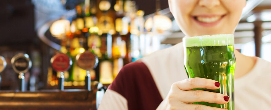 alcohol drinks and st patrick's day concept - close up of woman with green beer in glass over bar background