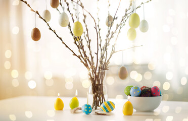 holidays and object concept - pussy willow branches decorated by easter eggs in vase and candles on...