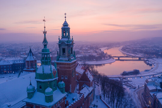 Wawel Royal Castle in winter. Snow on roofs and spires of Wawel castle cathedral and Vistula river in Krakow Poland city center at sunset.