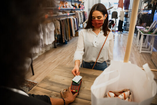 Customer in clothes shop pays to saleswoman at cashier with credit card with contactless payment wearing protective face masks during global Coronavirus Covid-19 pandemic
