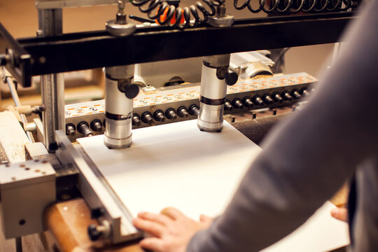 A drilling machine makes a hole in a wooden slab. Production and manufacture of wooden furniture in furniture factory.