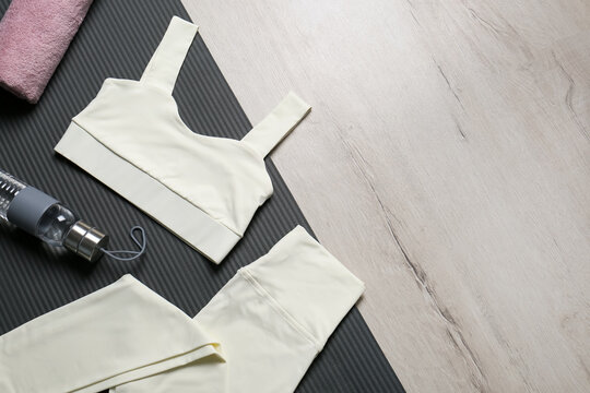 Stylish sportswear, bottle of water and yoga mat on white wooden background, flat lay. Space for text