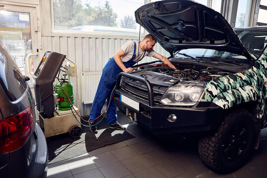 Mechanic connects air conditioning system on auto service