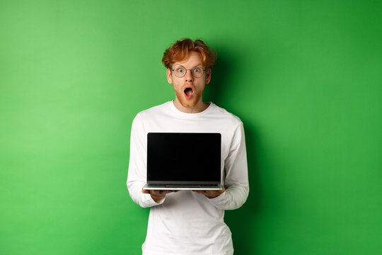 Surprised redhead man in glasses showing laptop blank screen, showing online promo and drop jaw, staring at camera amazed, green background