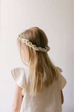 Blonde haired girl wearing a daisy crown seen in front of a empty neutral white background wearing a white summer blouse with her back turned to the camera.