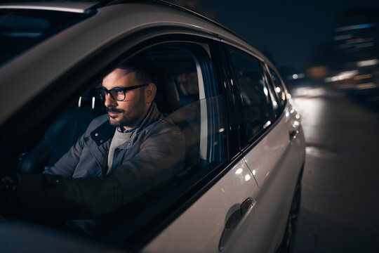 Handsome caucasian driving car at night