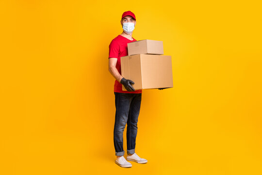 Full length body size view of nice guy mailman carrying big parcel wear mask social distance stop pandemia isolated over vivid yellow color background