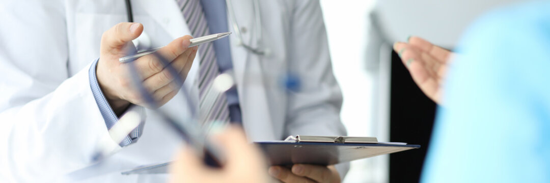 Doctor with phonendoscope holds pen and folder with documents in closeup conversation with another doctor. Medical advisory concept.