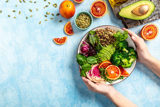 Girl holding Vegan, detox Buddha bowl with quinoa, micro greens, avocado, blood orange, broccoli, watermelon radish, alfalfa seed sprouts. Top view, flat lay, copy space
