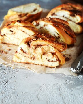 Cinnamon twisted loaf bread or babka on a dark wooden background, still life, rustic style