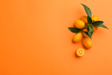 Fresh ripe kumquats with green leaves on orange background, flat lay. Space for text