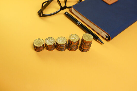 Coins stacked on the yellow background with a pen, notebook, and eyeglasses at the back