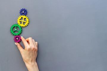 Fototapeta Working gears cogwheels mechanism in hand. Business problem solution and teamwork concept obraz