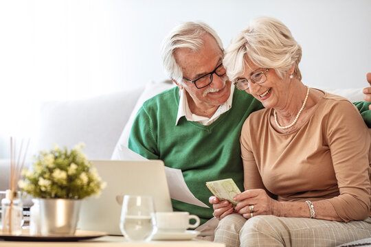Overjoyed exited middle aged married couple, finishing doing domestic paperwork together at home. Euphoric happy older mature spouses celebrating successful investment or purchase.