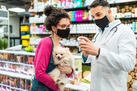 Female customer with protective face mask talking with veterinarian in pet shop and holding cute Pomeranian dog.
