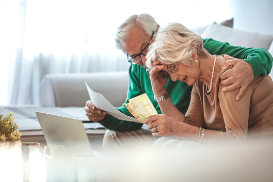 Senior couple at home with many bills. Worried Mature Couple Checking Finances And Going Through Bills Together. Shot of a senior couple working on their finances using a laptop.