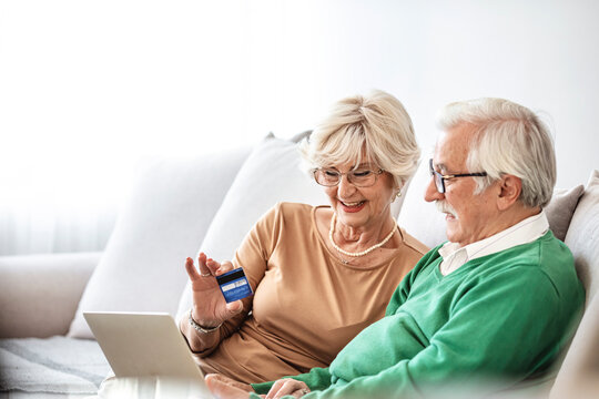 Senior couple checking bills using laptop at home. Close up of a senior couple online shopping at home. Happy senior couple talking while home shopping with laptop and credit card.