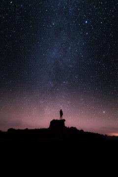 Silueta de una persona en la noche bajo las estrellas