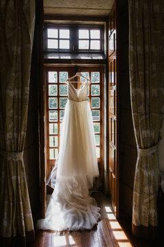 Bride dress pending on a window