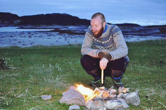 Man Crouching At Campfire On Field During Sunset