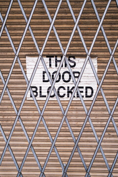 """""""This Door Blocked"""" sign on loading zone warehouse doorway"""